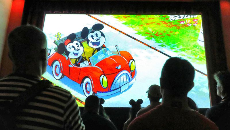 Guests watch the pre-show during a first look at Mickey & Minnie's Runaway Railway at Disney's Hollywood Studios.
